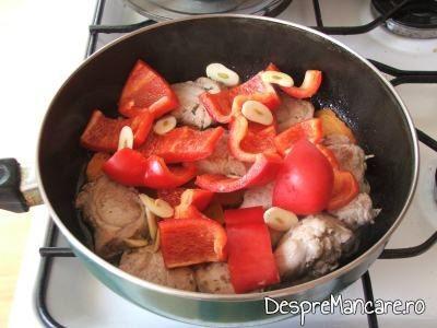 Adaugare de felii de ardei gras si feliute de usturoi pentru muschiulet de porc cu legume, la tigaie.