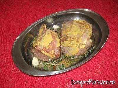 Bucati de spata prajita, unse cu mustar, asezate in tava, pentru spata de porc cu legume si costita, la cuptor.