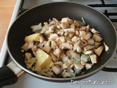 Cozile ciupercilor, ceapa rondele si usturoiul feliat subtire la calit, pentru ciuperci invelite in costita afumata, la cuptor.