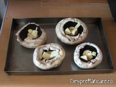 Adaugare unt proaspat in palariile ciupercilor pentru ciuperci invelite in costita afumata, la cuptor.
