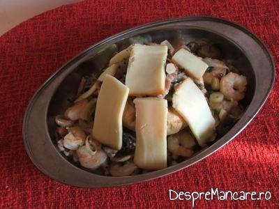 Felii de cascaval afumat asezate peste ciupercile mari pentru ciuperci umplute, pe pat de creveti, la cuptor.