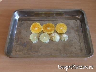 Felii de lamai si de portocale asezate pe fundul tavii pentru crap cu legume, lamai si portocale la cuptor.