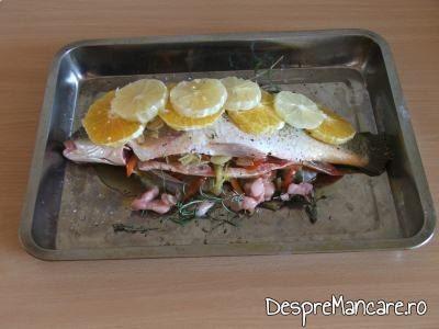 Felii de lamai si de portocale asezate pe peste pentru crap cu legume, lamai si portocale la cuptor.