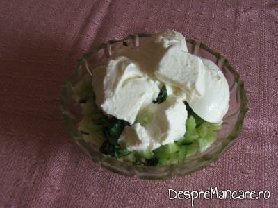 Adaugare iaurt peste castraveti si verdeata pentru pastrav umplut cu creveti plus legume la cuptor, cu sos de iaurt si castraveti.