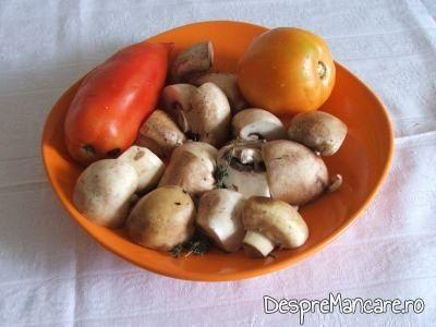 Rosii si ciuperci taiate in patru pentru pulpe cu legume si ciuperci la cuptor.