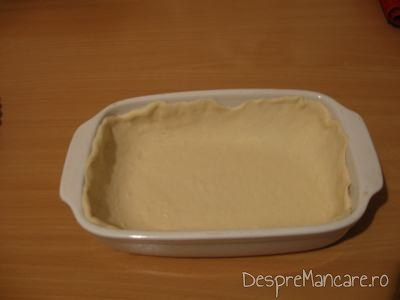 Aluat intins in vasul de copt pentru tarta cu varza, prosciuto si ou batut.