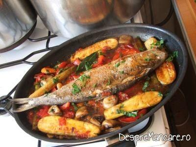 Preparatul scrumbie de Dunare cu legume si ciuperci, la tigaie, se stropeste cu cateva picaturi de vin alb sec.