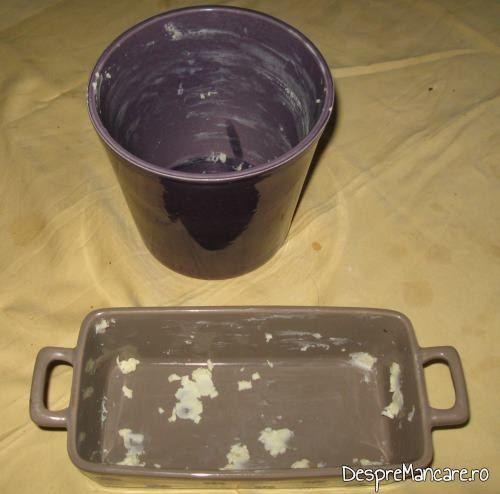 Vasele din ceramica, unse cu unt proaspat, pregatite pentru coacere paine de casa umpluta cu porcarele, cascaval si masline.