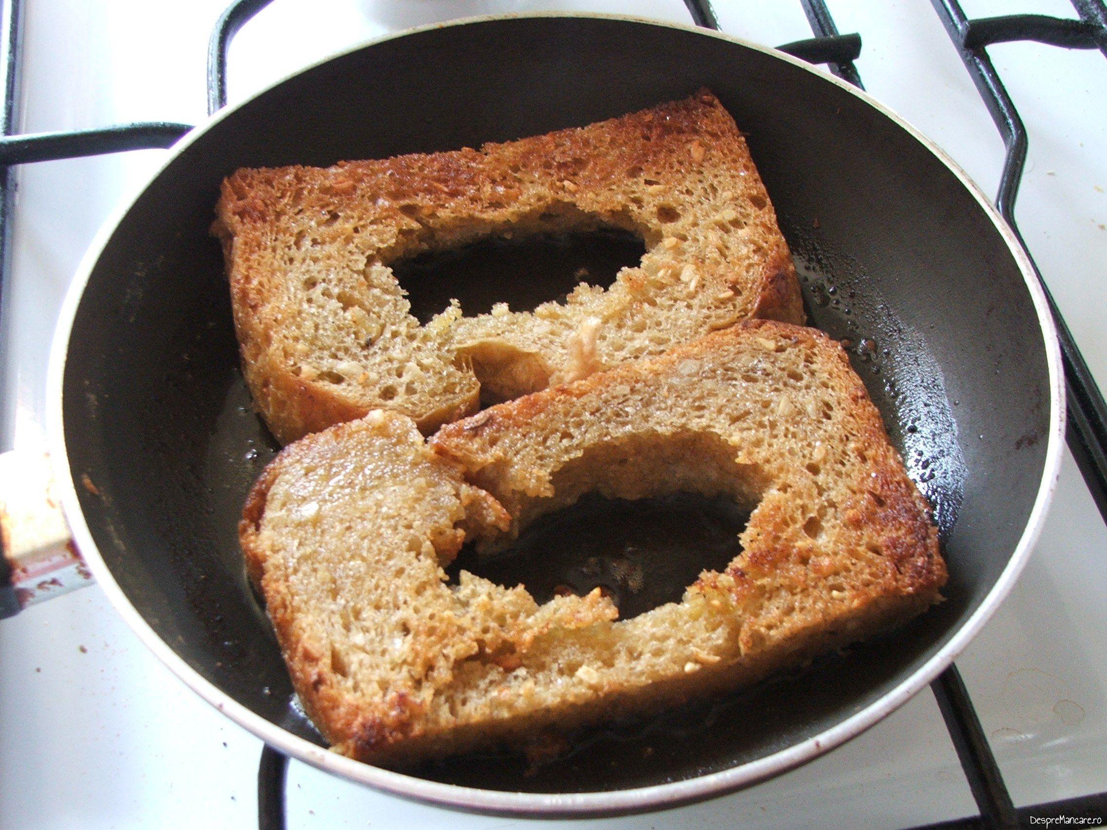 Felii de paine care se prajesc in amestec de ulei de masline si unt proaspat, pentru ochiuri cu cascaval afumat si paine prajita.
