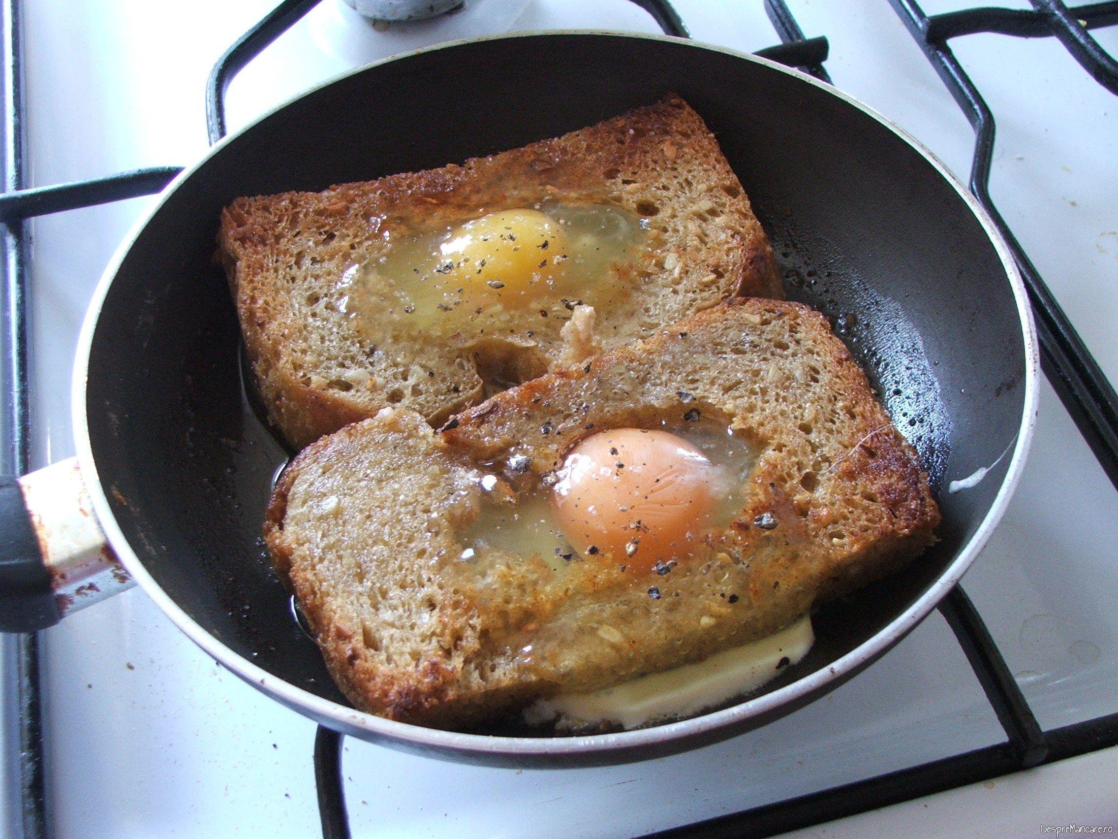 Oua de gaina scoase din coaja, puse in gaura de la feliile de paine pentru ochiuri cu cascaval afumat si paine prajita.