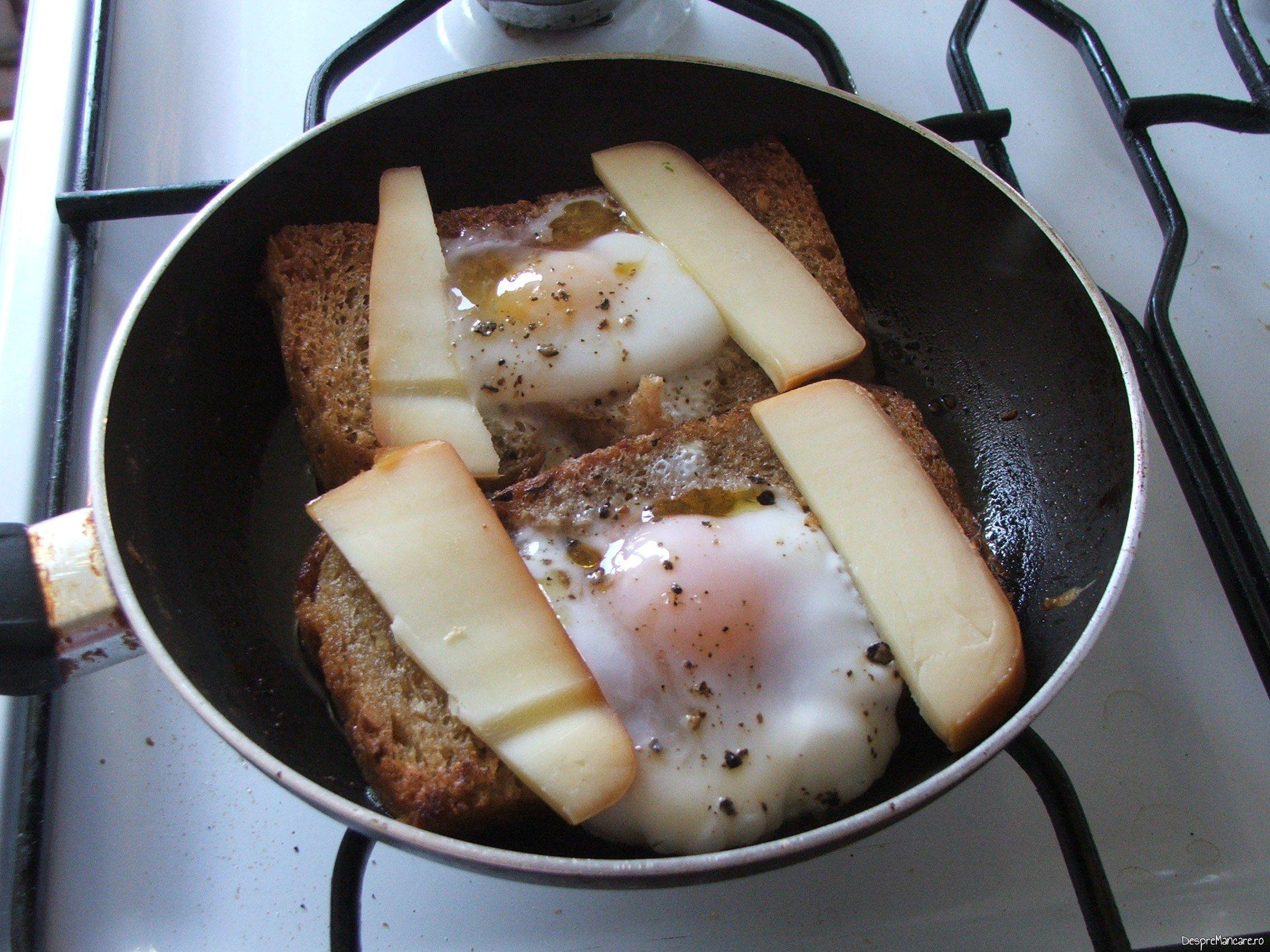 Felii de cascaval afumat puse pe felii de paine, langa ochiuri pentru ochiuri cu cascaval afumat si paine prajita.