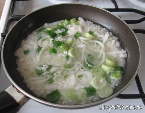 Ceapa verde se caleste impreuna cu orezul prefiert pentru sarmalute in foi de vita.