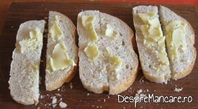 Felii de paine integrala unse cu unt pentru pregatirea crutoanelor folosite la supa crema de legume cu crutoane si cascaval afumat.