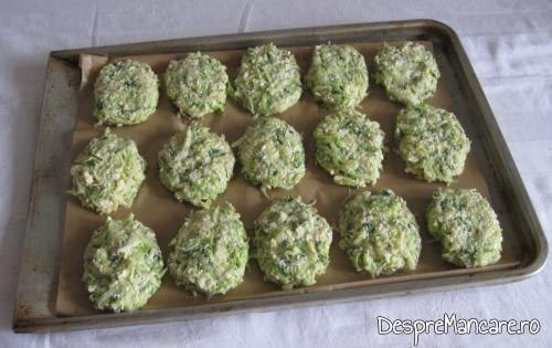 Chiftelute din legume, asezate in tava, pe hartie de copt, pentru a fi introduse in cuptor.