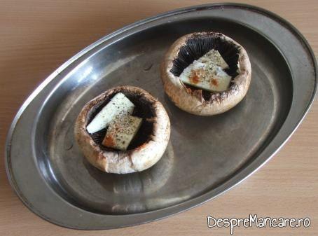 Felii subtiri de unt si cascaval puse in palaria ciupercii pentru preparare ciuperci cu ou si cascaval la cuptor.