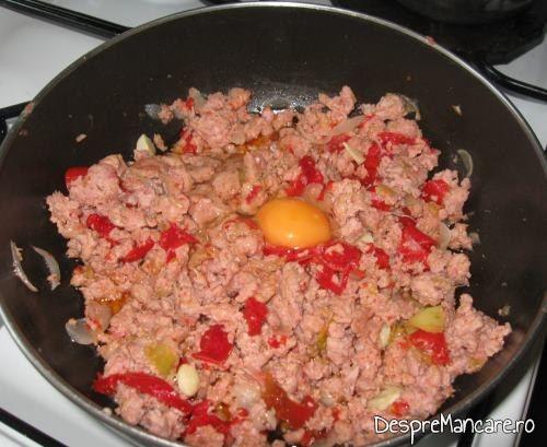 Carne tocata de curcan, ceapa prajita, ardei gras si ou, care se amesteca pentru varza noua cu carne tocata de curcan, la cuptor.