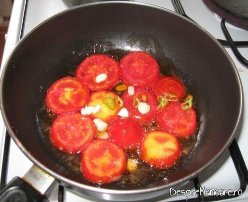 Felii de rosii, impreuna cu feliute de usturoi si ardei iute care se calesc in ulei de masline pentru omleta cu rosii.