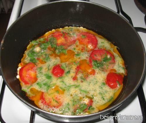 Ouale batute adaugate peste rosiile calite pentru omleta cu rosii.