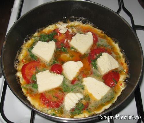 Felii subtiri de telemea de oaie/ capra si/ sau cascaval afumat adaugate in ouale batute pe jumatate coapte pentru omleta cu rosii.