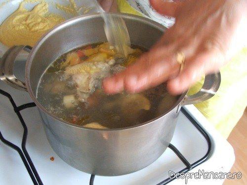 Adaugare in supa fierbinte, din amestecul de gris si ou batut pentru galuste, la supa de gaina cu rosii si galuste.