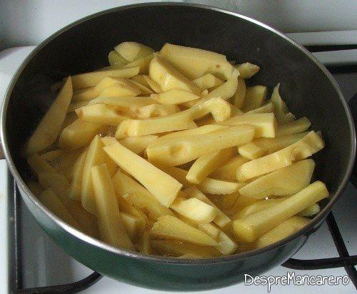 Garnitura de cartofi prajiti pentru muschiulet si carnat de porc cu legume, la tigaie, in sos de smantana este aproape gata.