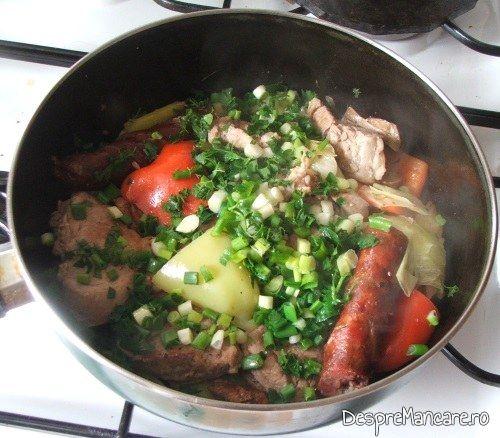Adaugare verdeata pe muschiulet si carnat de porc cu legume, la tigaie, in sos de smantana.