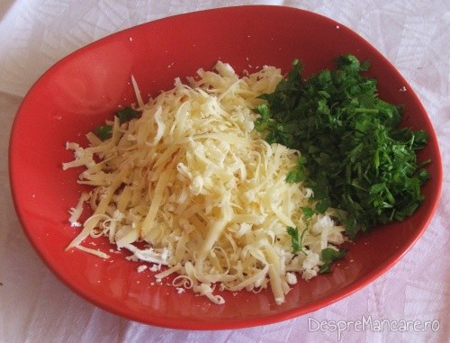 Branza de oaie si cascaval afumat, date pe razatoare si verdeata tocata pentru vinete impanate cu legume, la cuptor.
