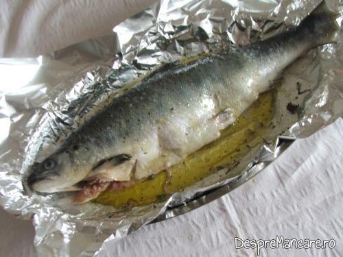 Somon gata pregatit pentru a fi introdus la cuptor pentru somon la cuptor cu legume si ciuperci la tigaie.