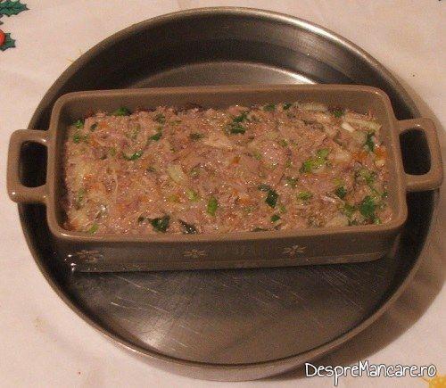 Vasul termorezistent, cu ingrediente pentru terina din costita si carne afumata de porc, legume si carne de vitel, fierte., pus intr-o tigaie cu apa fiarta, pentru introdus la copt.