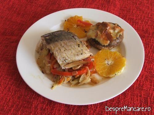 Pastrav somonat cu legume si citrice in hartie de copt, la cuptor servit pe farfurie.