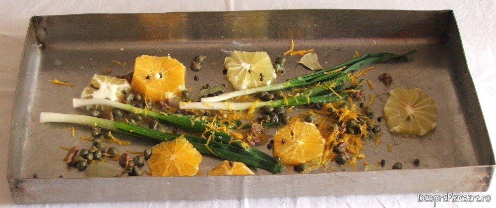 Citrice felii, fire de ceapa si usturoi verde, boabe de piper, foi de dafin, ansoa, capere, coaja de lamaie si de portocale puse in tava de copt pentru avat cu citrice la cuptor, cu garnitura de ciuperci.