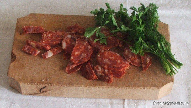 Carnatii picanti taiati felii si verdeata pentru budinca cu branza, praz si carnati picanti.