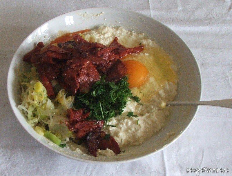 Ingredientele gata amestecate pentru budinca cu branza, praz si carnati picanti.