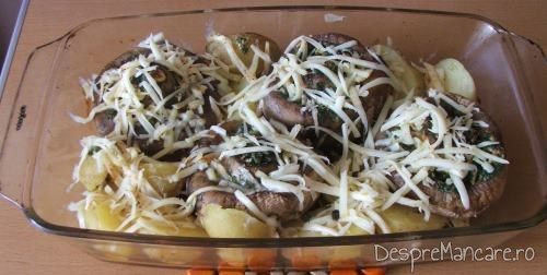 Cascaval ras adaugat peste cartofi si ciuperci umplute, in vasul de copt pentru cartofi noi si ciuperci umplute, la cuptor.