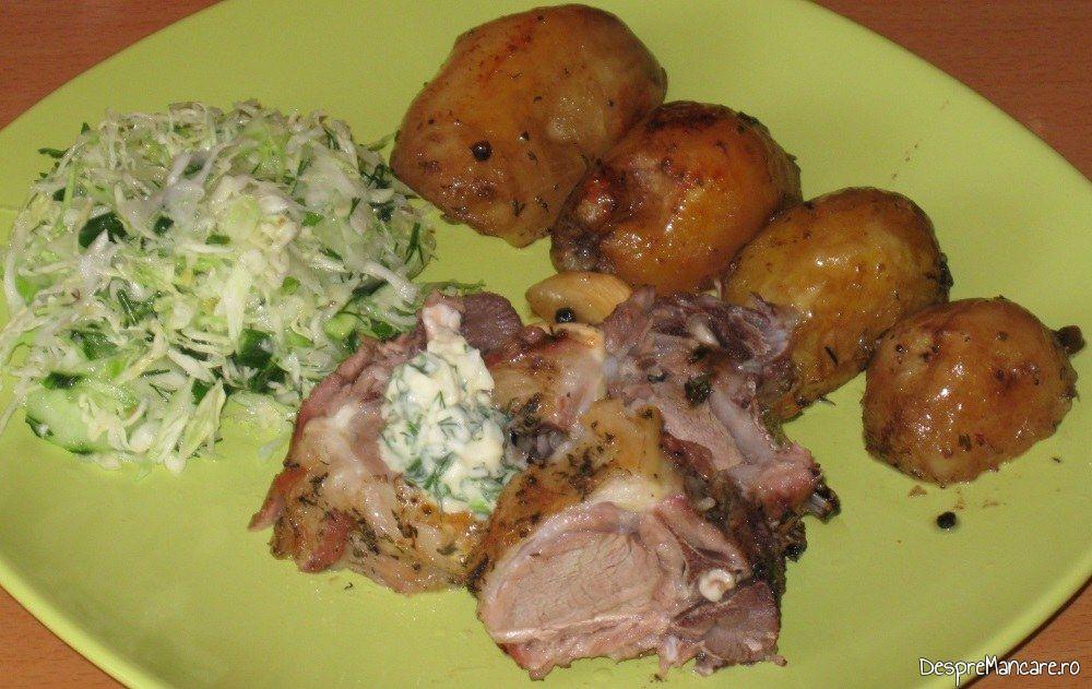 Cotlet de ied cu cartofi, la cuptor servit pe farfurie incalzita cu salata de varza noua.
