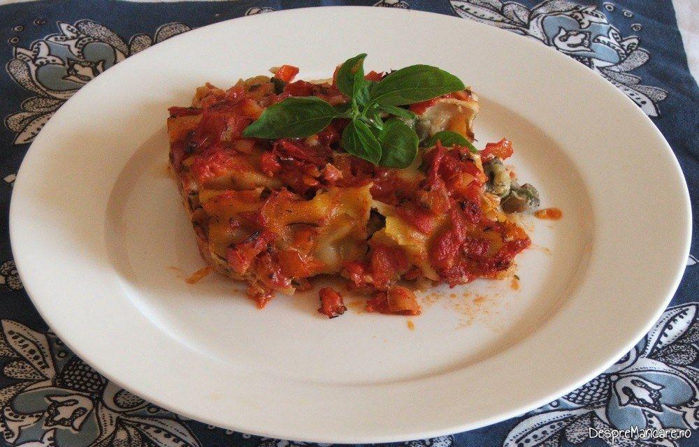 Paste cannelloni umplute cu ciuperci in sos de rosii servite calde, decorate cu frunze de busuioc.