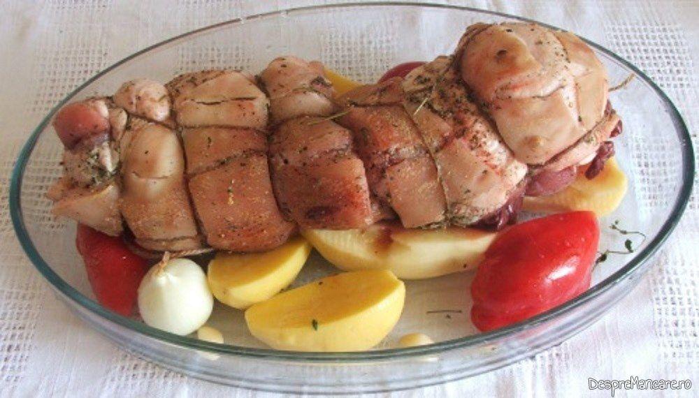 Rulada din fleica de porc cu sorici si ficatei de curcan impreuna cu legumele, in vasul de copt.