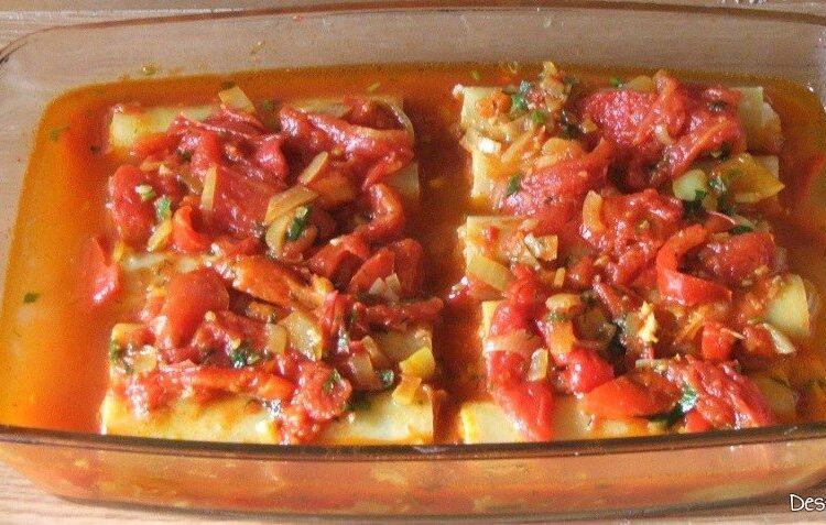 Paste cannelloni umplute cu peste, in sos de rosii pregatite pentru a fi introduse in cuptorul aragazului.