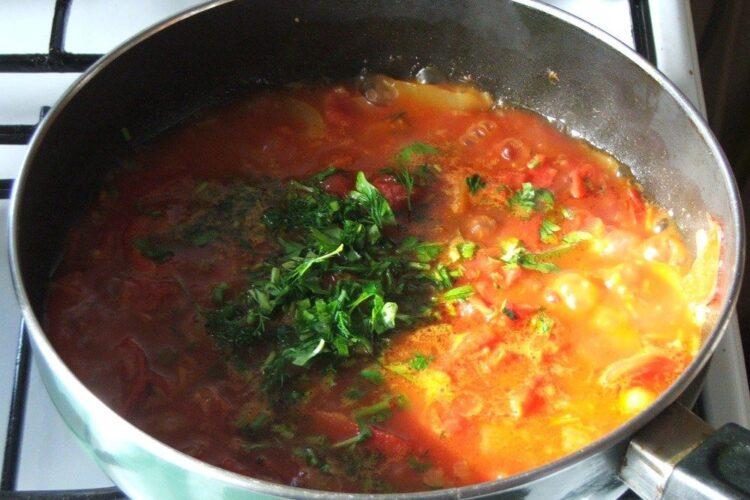 Adaugare verdeata in sosul de rosii pregatit pentru paste cannelloni umplute cu peste, in sos de rosii.