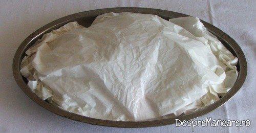 Legume asezonate si tavalite prin amestec de ulei de masline si zeama de lamaie acoperite cu hartie de copt pregatite pentru a fi introduse in cuptorul aragazului.