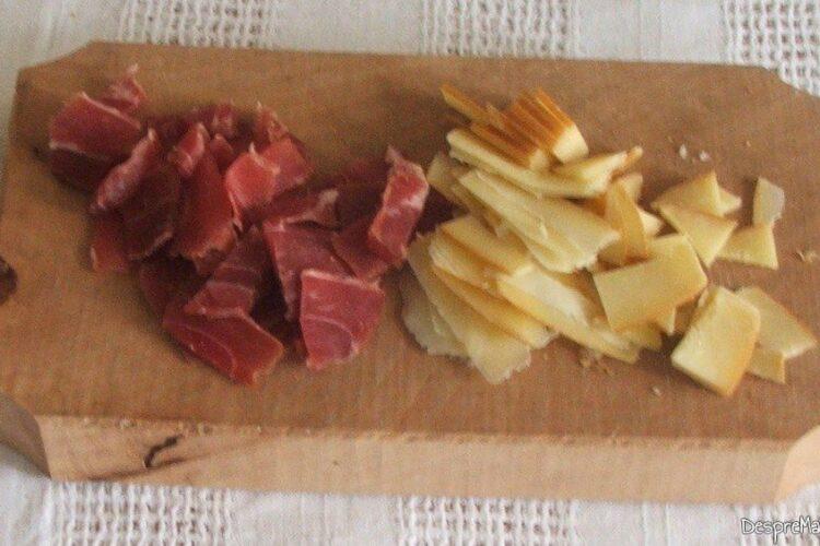 Carne si carnati afumati, cascaval afumat, taiate bucati potrivite pentru creier de porc cu porcarele, cascaval si parmezan, la cuptor.