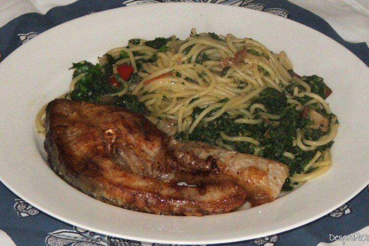 Spaghete cu sos de urzici si peste prajit - preparatul este servit.
