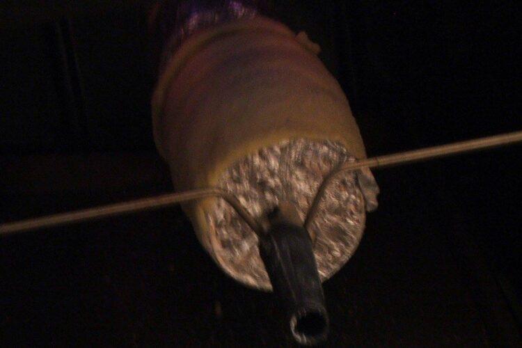 Fixare tija rotisor cu cutiile de bere prinse de tija, in dispozitivul pentru rotisor al aragazului.