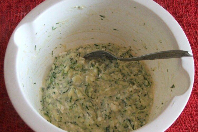 Amestec de dovlecei dati pe razatoare, branza, oua si verdeata pregatit pentru prajire.