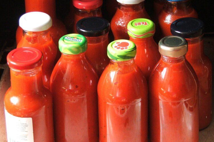 Sticlute si borcanele cu pasta de ardei si rosii depuse in cuptorul aragazului pentru sterilizare.