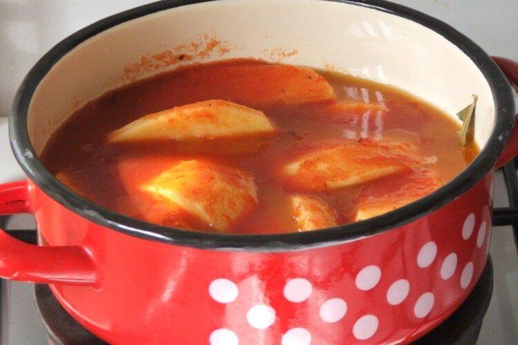 Fierbere cartofi in suc de rosii pentru mancare de cartofi cu ceafa de porc la gratar.