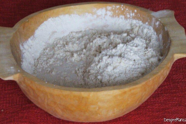 Amestec de faina, unt si iaurt care incepe a prinde consistenta aluatului pentru paine.