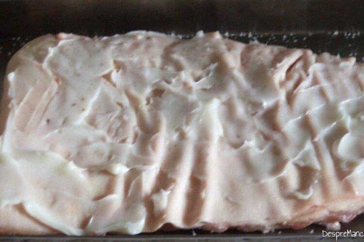 Coasta de purcel asezonata pe partea cu carne si unsa cu untura de porc pe partea cu sorici, asezata in tava de copt, pregatita pentru coacere.