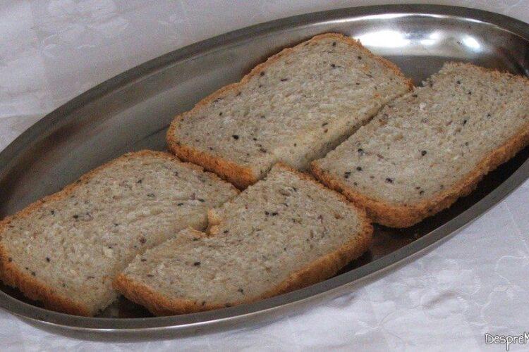 Felii de paine neagra, cu seminte puse in tava pentru prajire.
