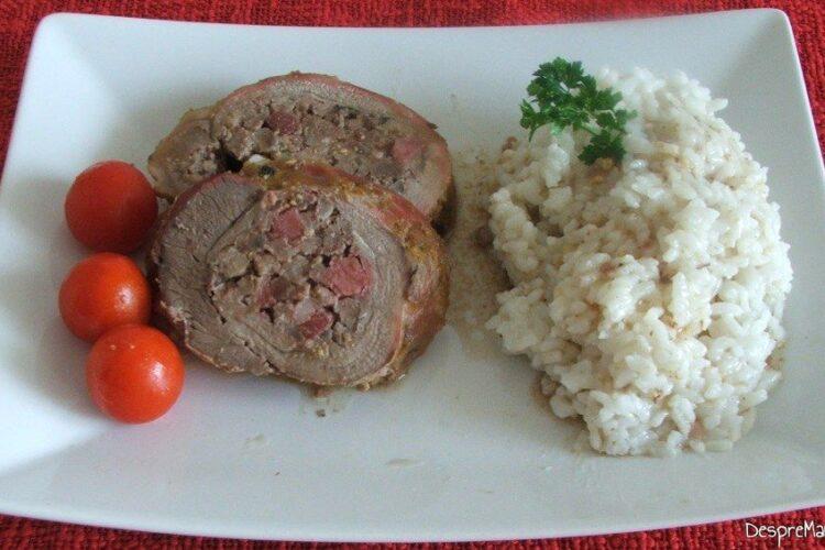 Servire rulada din pulpa de vitel cu carne tocata de porc si piept de porc cu garnitura de orez.